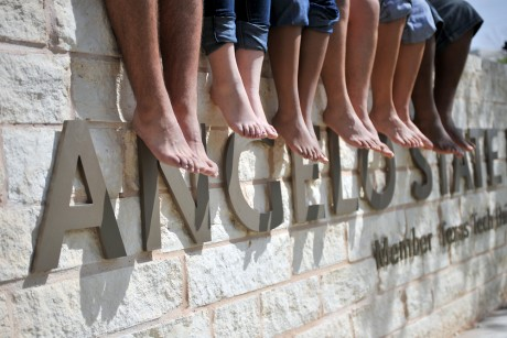 International students dangle their bare feet in front of an Angelo State University sign.